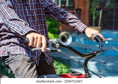 Man behind the wheel of the bicycle presses on the brake close-up. Old manual air horn signal