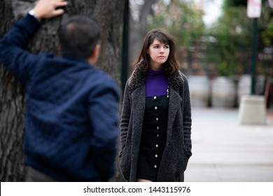 Man being rude, leering and cat calling or sexually harassing a woman walking on the street.  Also depicts crime and safety with a stalker following a female victim.