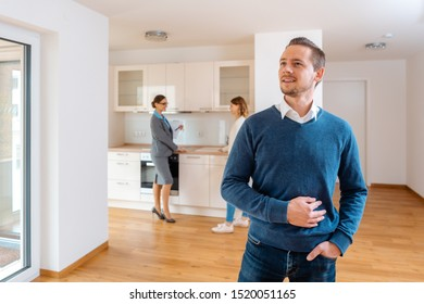 Man being satisfied with the new apartment he wants to buy, realtor and his wife in the background