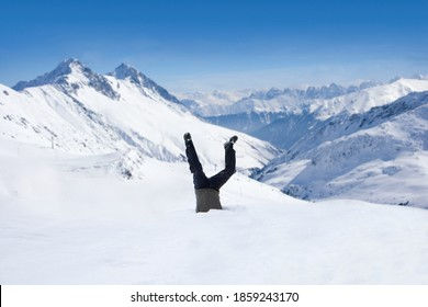 Man being in upside-down position inside a hole dug in the snow at the top of a remote mountain