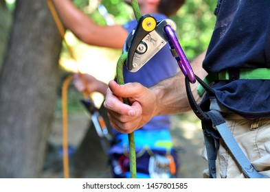 Man belaying during climbing, close-up of hand and protection device (gri-gri). Concept of connection, safety, control, outdoor activity. Climber with partner.