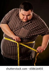 Man belly fat with tape measure weight loss around body on black background. First day of diet. Person is obese.