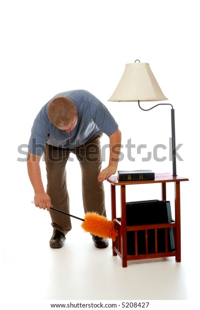 Man bending over to dust a side table with lamp.  Isolated on white.