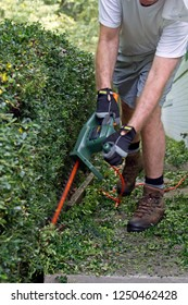 A man bent over in motion as he wields electronic pruning shears to prune a long hedge in summertime