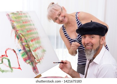 Man in beret sits in front of an easel and smiles at the camera