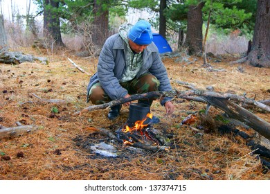 Man beside campfires in spring wood