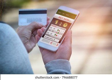 Man betting on sports, holding smart phone with working online betting mobile application