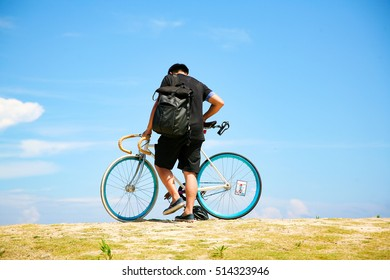 a man with bicycle on green grass under blue sky