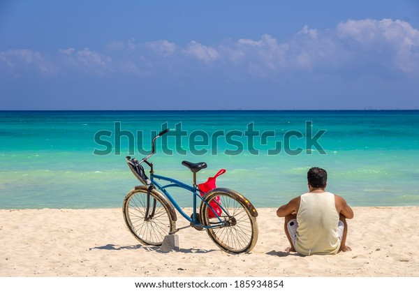 Man with bicycle on a tropical beach