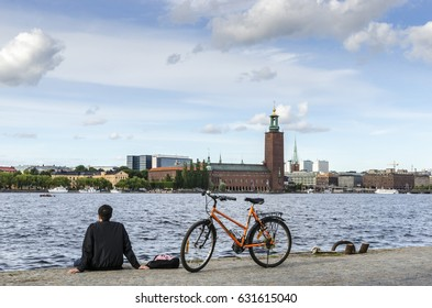 Man with a bicycle opposite the City Hall (Stadshuset) in Stockholm, Sweden