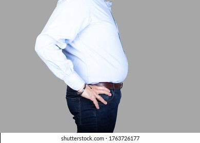 man with a big belly and overweight is wearing a shirt and jeans, side view