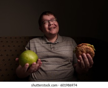 Man with big belly thinking of what to eat - apple or burger. Obesity and gluttony,