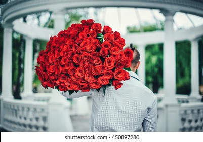 man with big bouquet of roses outdoor