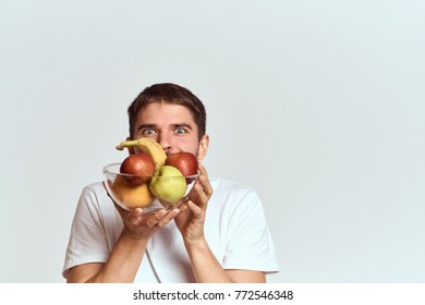 man with big eyes holding a plate of fruit