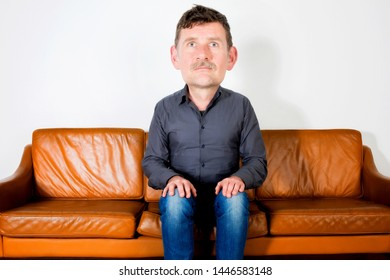 man with big head in his 50s sitting on couch and waiting