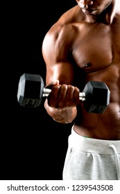 man big muscles doing exercises with dumbbells over black background