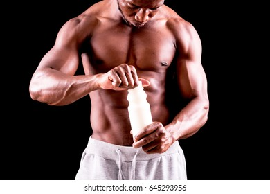 man big muscles with  milk bottle over black background