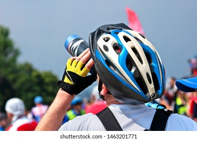 man in bike security helmet drinks water in bycicle competition in sunny day