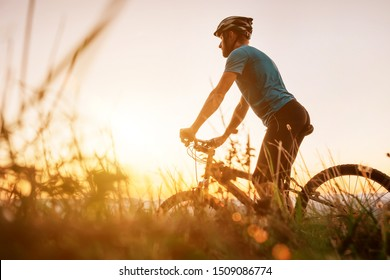 Man biker man meets a sunset in top of hill over the city. Active sport people concept image
