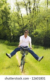man biking in park, smiling and outstretching his legs
