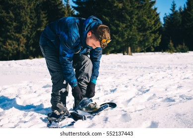 man binding snowboard