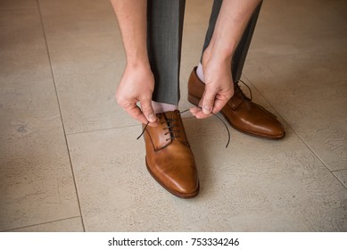 Man binds laces at brown boots