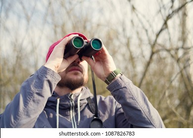 Man with the binoculars against the background of the nature. Observation of birds. Birdwatching