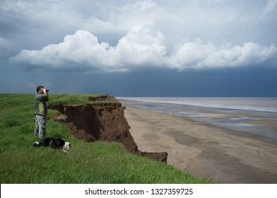 Man with binoculars and dog birdwatching, wildlife watching on coast cliff edge with dramatic sky looking out to sea over a sandy beach. - Image