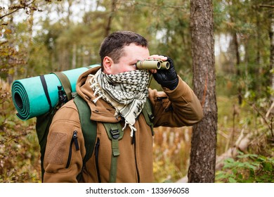 Man with binoculars at a forest.