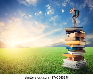 Man with binoculars over a pile of books observe a colorful sunrise. the culture open the imagination