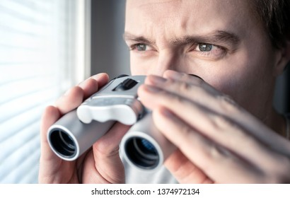 Man with binoculars. Private detective, agent or investigator looking out the window. Man spying or investigating. Privacy, surveillance or espionage concept. Suspicious or curious person spying.