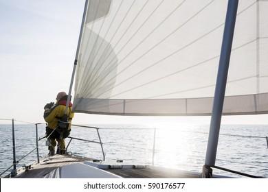 Man With Binoculars Sailing On Yacht In Sea