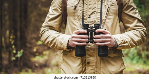 Man with binoculars standing in the woods.