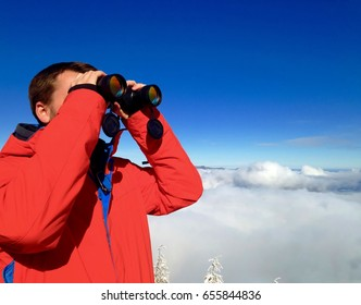 Man with binoculars watching mountains in winter.