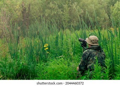man birdwatcher makes field observation with a spotting scope standing among the tall grass