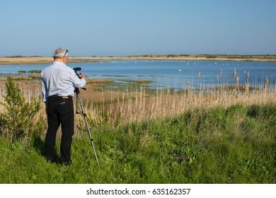 Man birdwatcher shoots video of birds in Shablaenska Tuzla - Via Pontica natural reserve