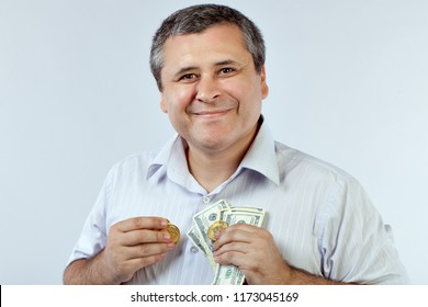 Man with bitcoins and dollars in his hands, a smile on his face.