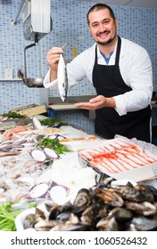 Man in black apron and white cover-slut behind counter holding fish