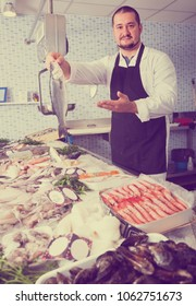 Man in black apron and white cover-slut behind counter holding fish supermarket