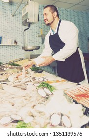 Man in black apron and white cover-slut behind counter holding fish  indoors
