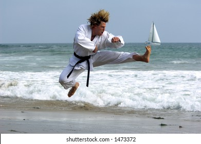 Man with a black belt working out on the beach. Executing a flying kick