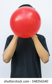 Man in black blowing red balloon