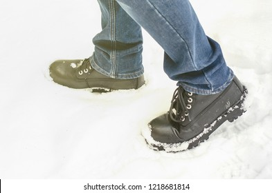 Man in black boots in deep snow. Winter concept. Cold spring
