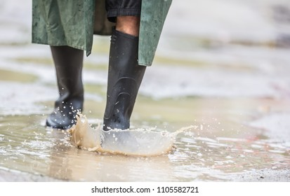A man with black boots walks on a flooded road.