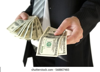 Man in black business suit, holding cash in hands.