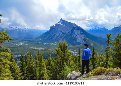 Man in black cap and blue jacket is watching down to the valley. View of town under the high peak. Mount rundle view from opposite viewpoint. Iconic viewpoint above town Banff of Rockies in Alberta.