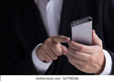 A man in black casual suit holding his mobile phone and touching the screen.