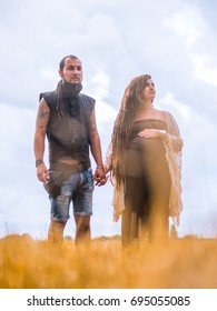 Man in a black cloth and pregnant woman in long dress with dreadlocks standing in wheat field on stormy sky background. Love story. Informal people with tattoo and piercing.