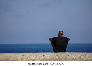 A man in black clothes relaxes sitting on a stone fence overlooking the sea and the endless horizon