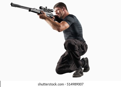 Man in black clothing with sniper rifle aiming isolated on white